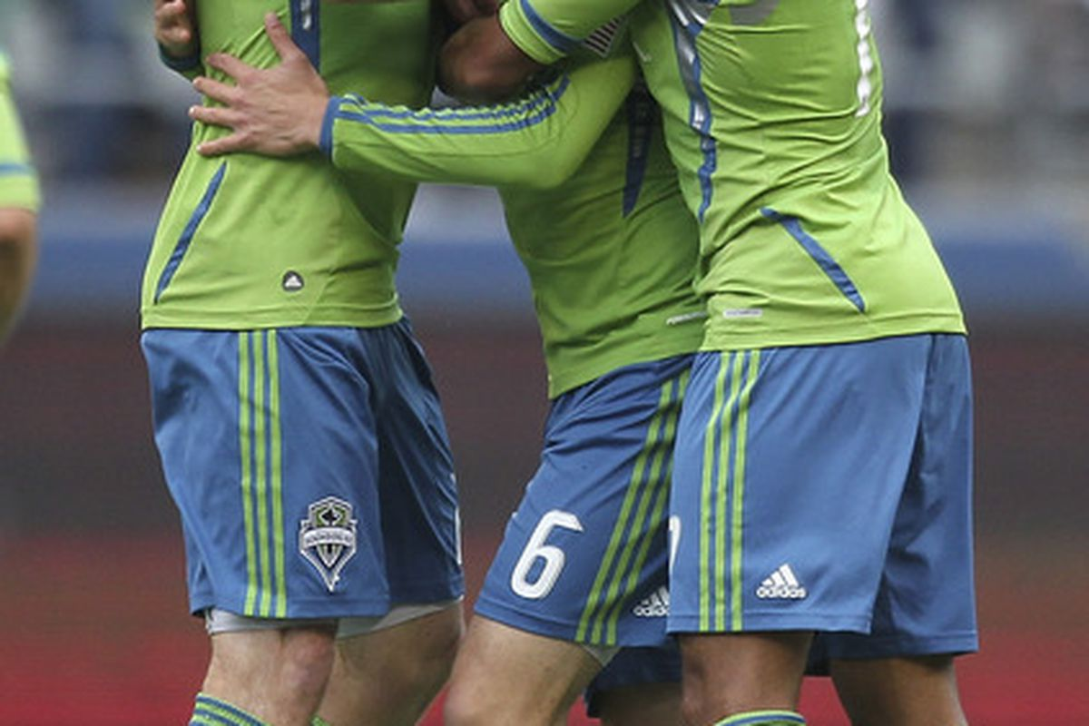 SEATTLE - JUNE 23:  Osvaldo Alonso #6 of the Seattle Sounders FC is congratulated by teammates after scoring a goal against the New York Red Bulls at CenturyLink Field on June 23, 2011 in Seattle, Washington. (Photo by Otto Greule Jr/Getty Images)