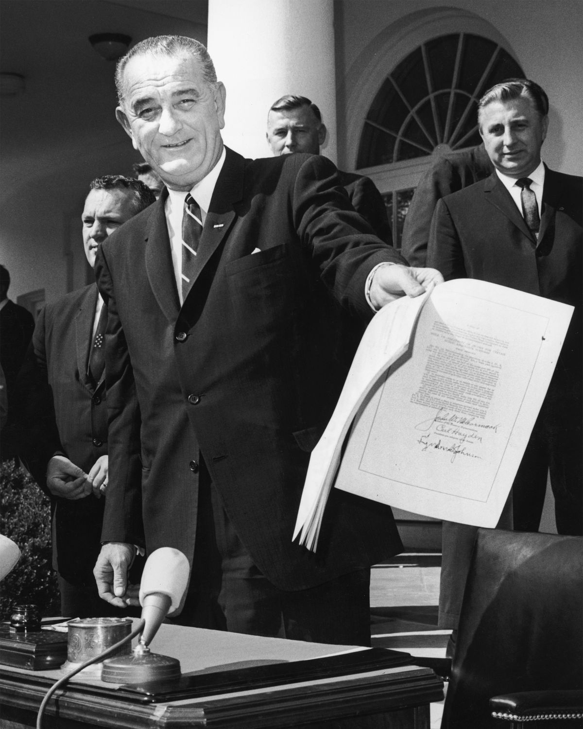 President Lyndon B. Johnson smiles and holds up a signed copy of the Economic Opportunity Act of 1964.