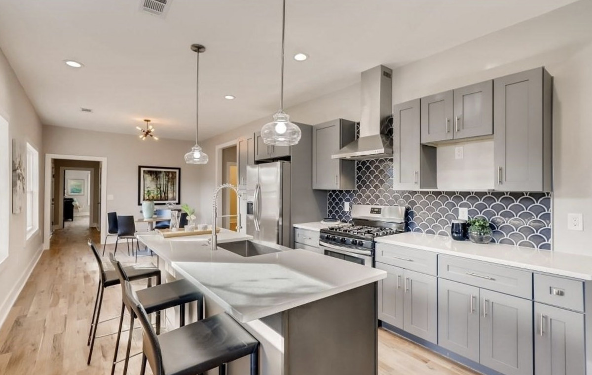 Kitchen with gray cabinets, tiled backsplash, pendant lights, and barstools along one counter.
