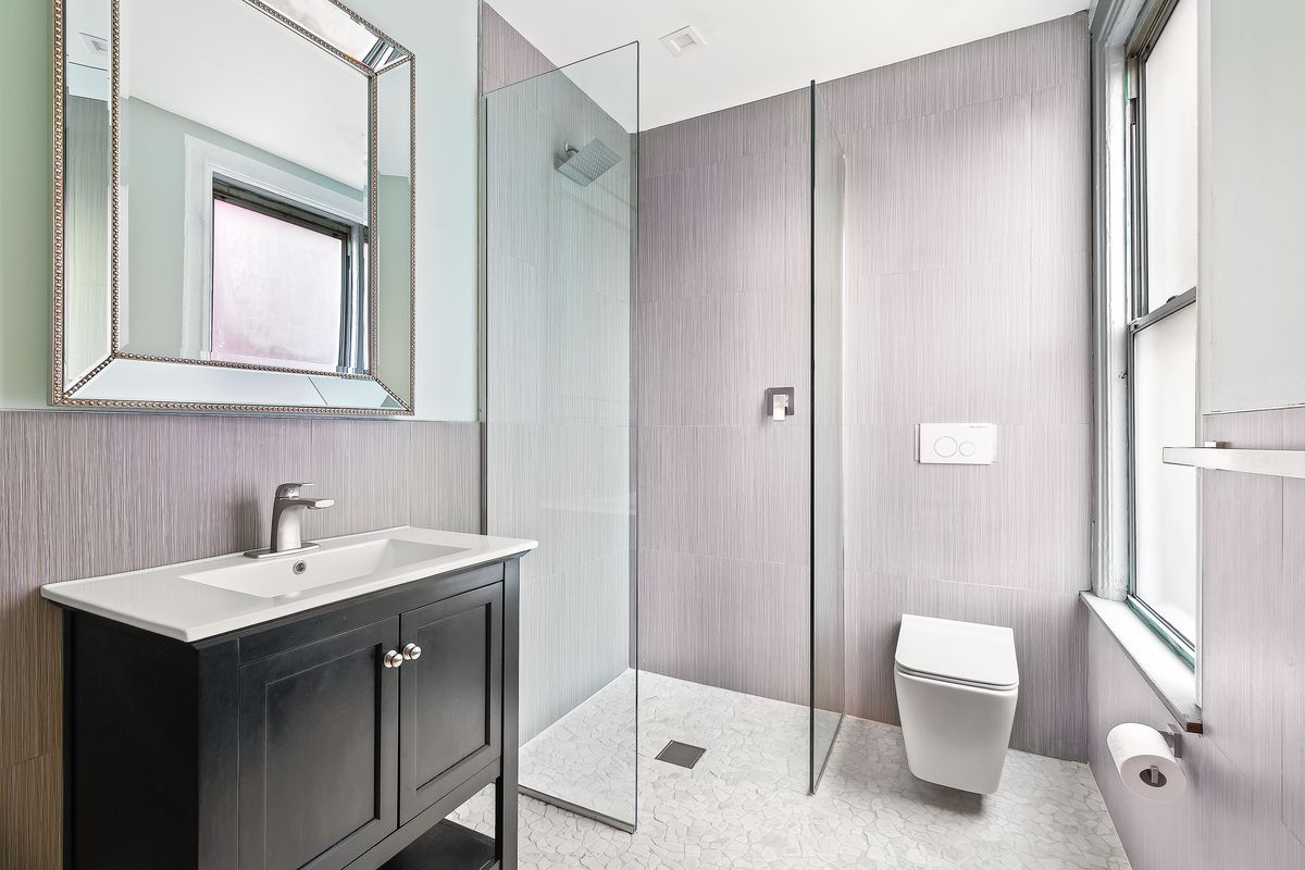 A bathroom with grey walls, a window, and a large mirror.