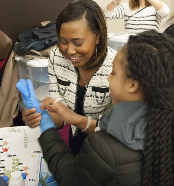 Metropolitan Water Reclamation District President Kari K. Steele assists a student during the Jr. Science Café in celebration of the Museum of Science and Industry's Black Creativity program exposing African-American youth to careers in science, technolog