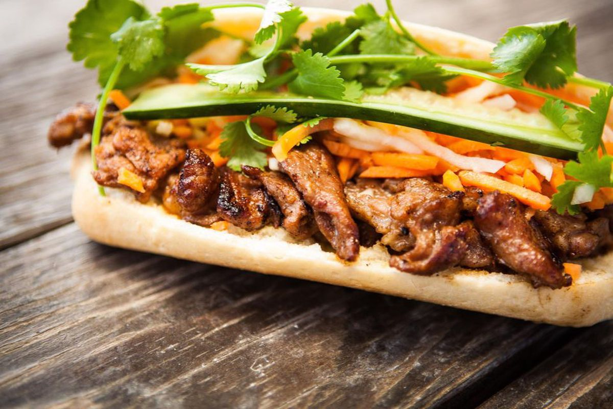 Closeup of a banh mi with meat, carrots, cucumber, and cilantro on a wooden picnic table