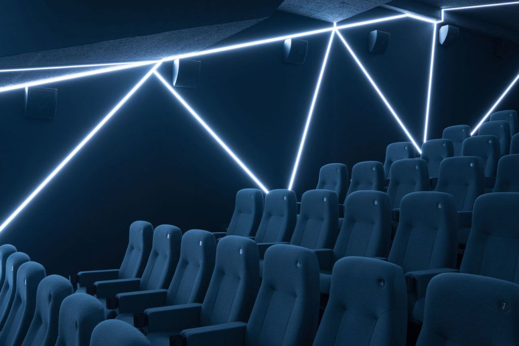 Theater with black chairs and fluorescent lights