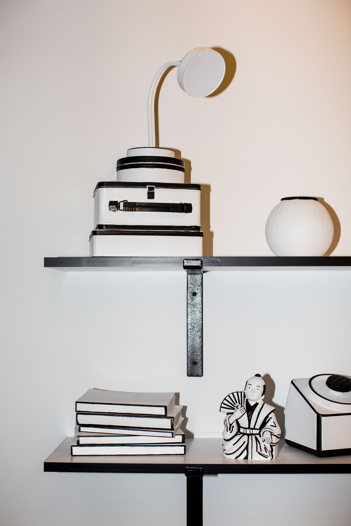 Dream Machine black and white shelf with a lamp, boxes, a pot, a stack of books, and other knick-knack decor.