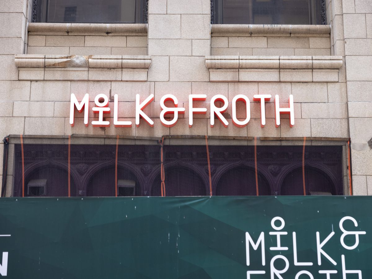 A sign reading Milk & Froth hangs on the outside of a brick building.