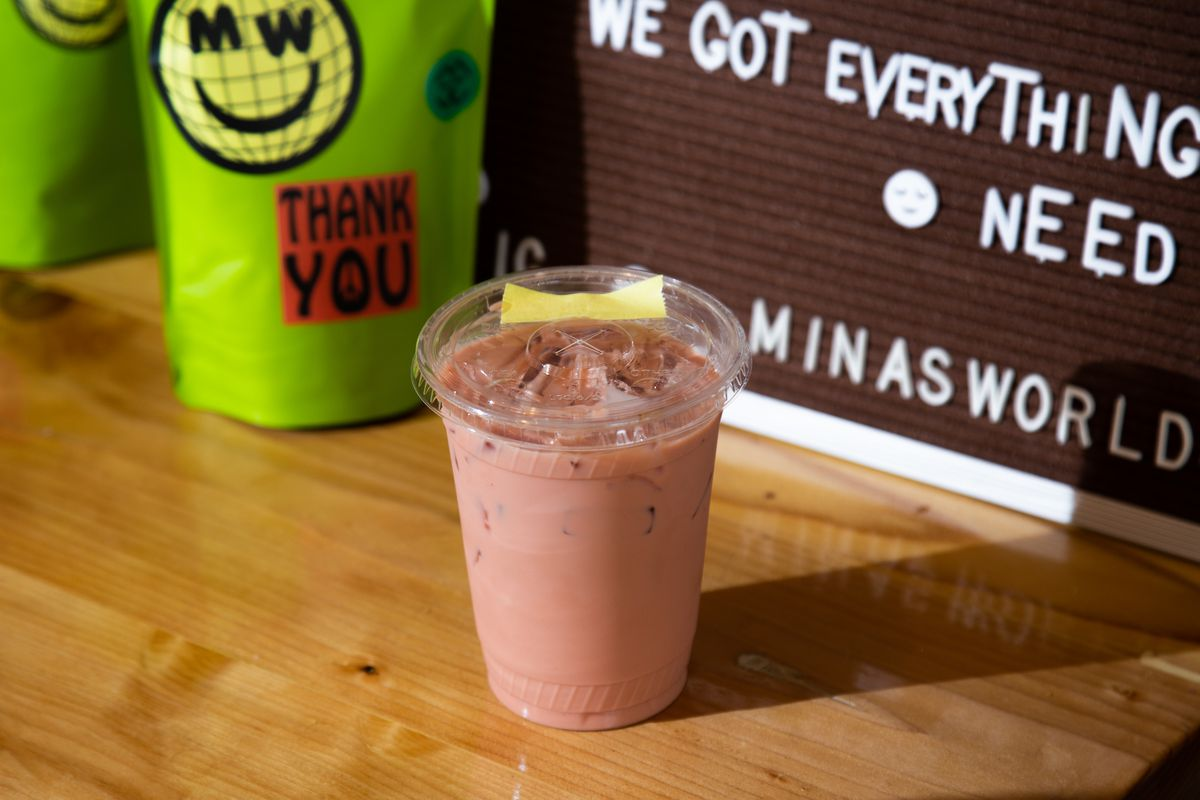 a pink iced latte in front of a board for minas world that reads we've got everything you need and bags of green coffee