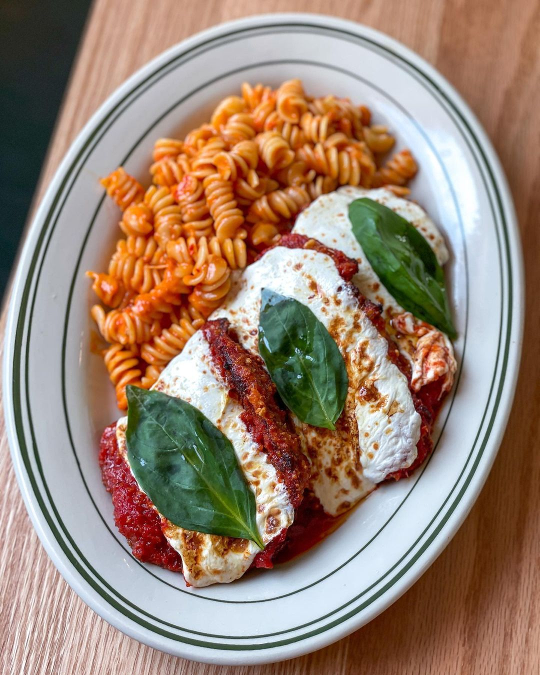 Overhead view of chicken parm on a white plate with a side of rotini. The plate is on a light wooden surface.