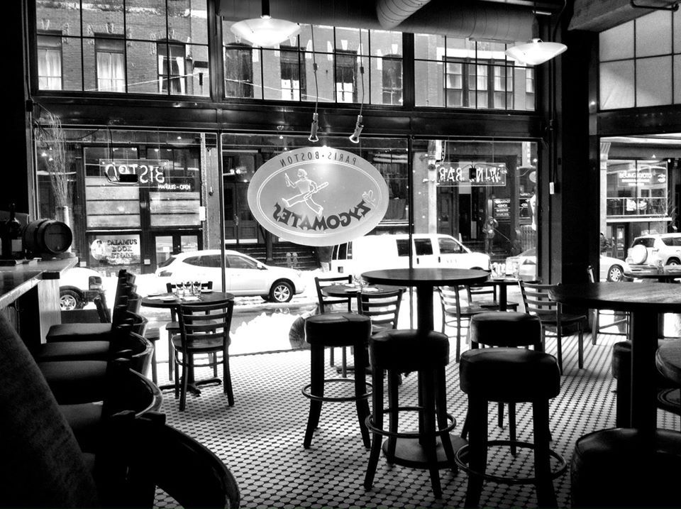 black and white photo of a restaurant interior with a checkered tile floor and a French bistro feel