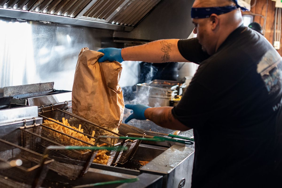 A man wearing a bandana pours fries into a fryer.