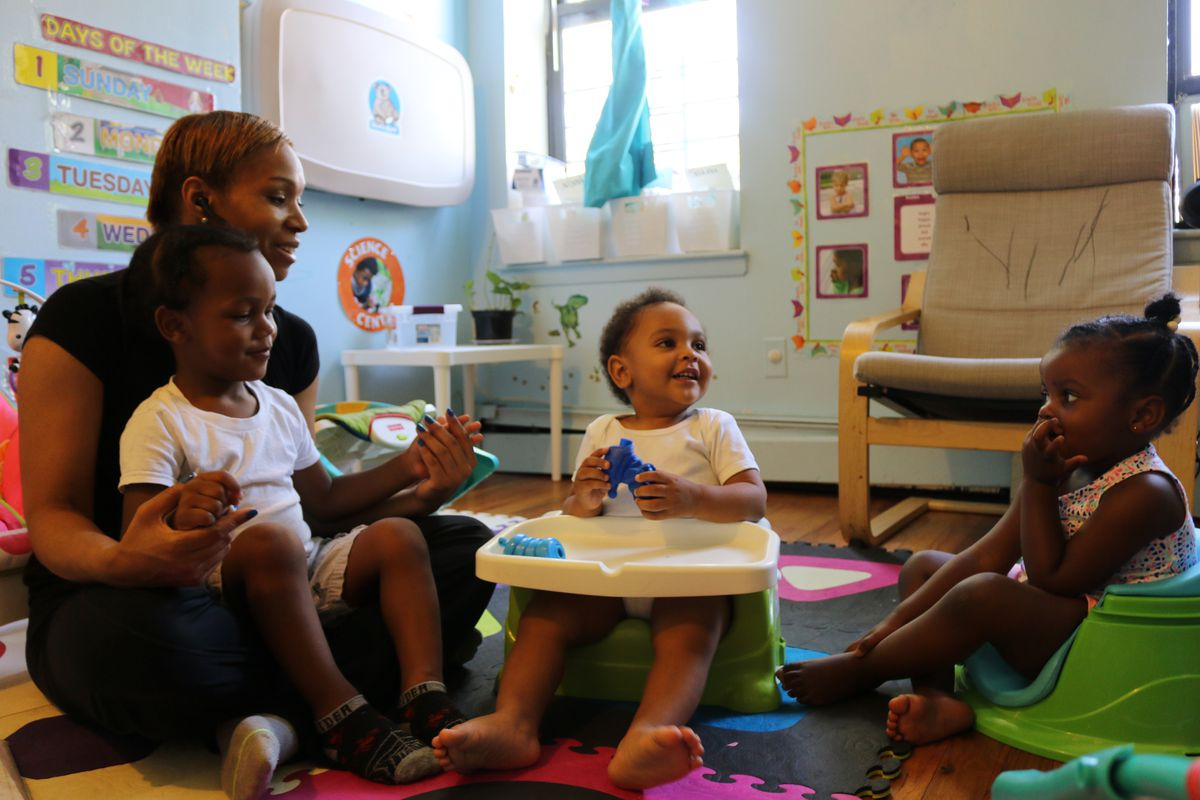 Sherease Alston sings along with children at her child care center, Little Minds at Work.