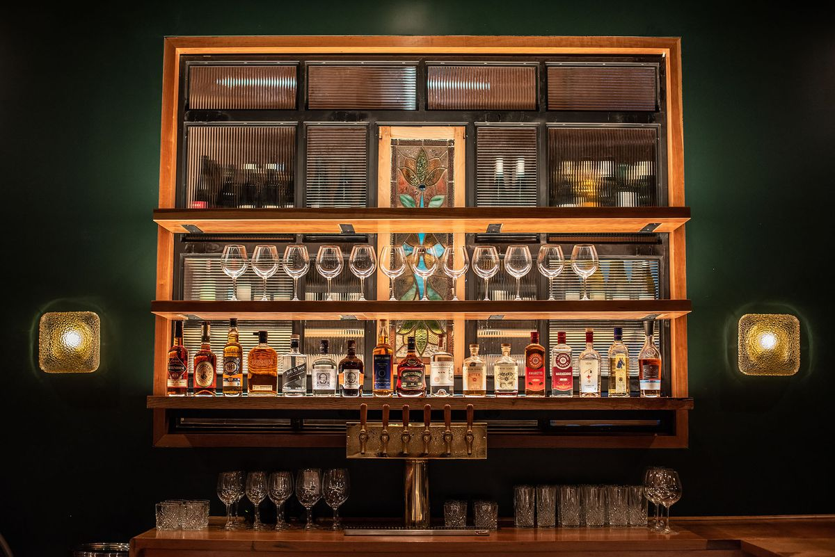 A glowing back  bar lit up with glassware.