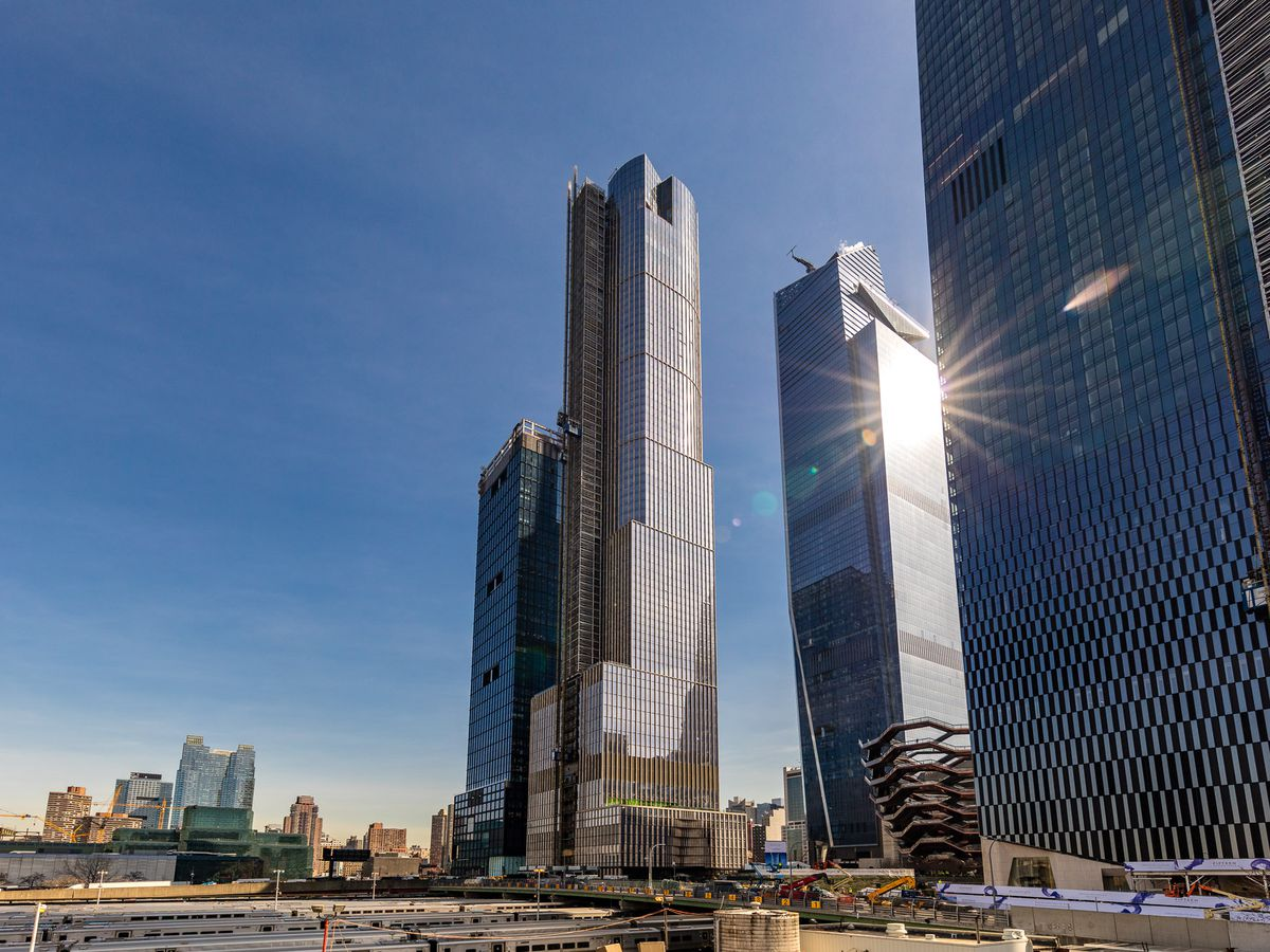 Several tall skyscrapers with glass exteriors, which sit next to a train yard.