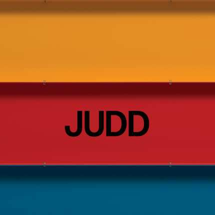 """Book with yellow, red, and blue stripe with """"JUDD"""" written on it."""