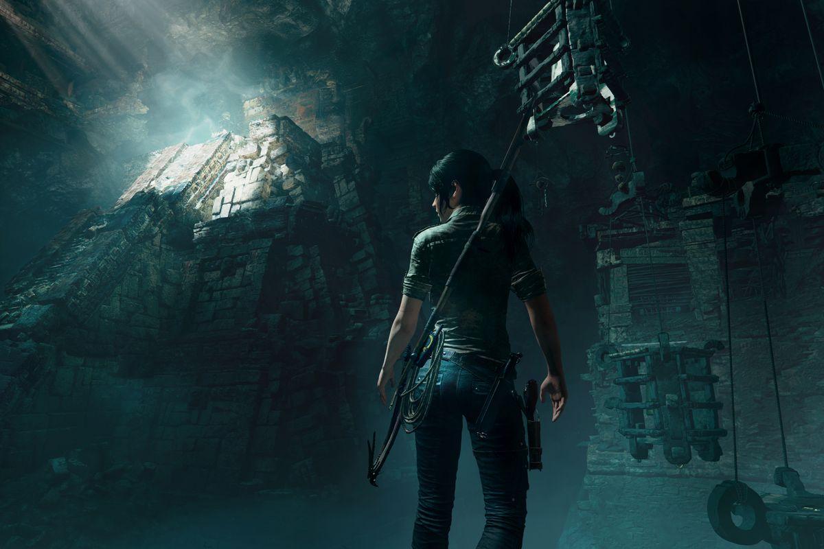Lara Croft surveys a dark temple in a screenshot from Shadow of the Tomb Raider