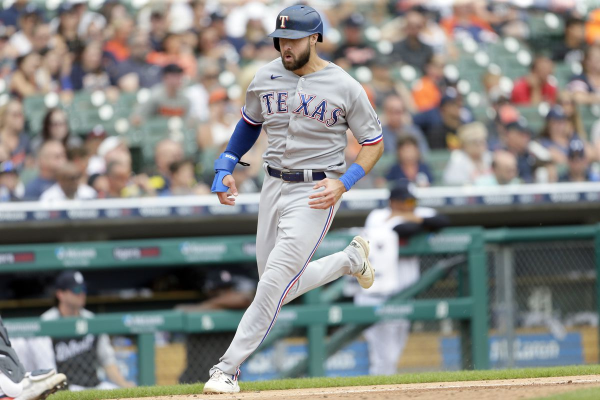 Joey Gallo #13 of the Texas Rangers scores against the Detroit Tigers on single by David Dahl during the sixth inning at Comerica Park on July 22, 2021, in Detroit, Michigan.