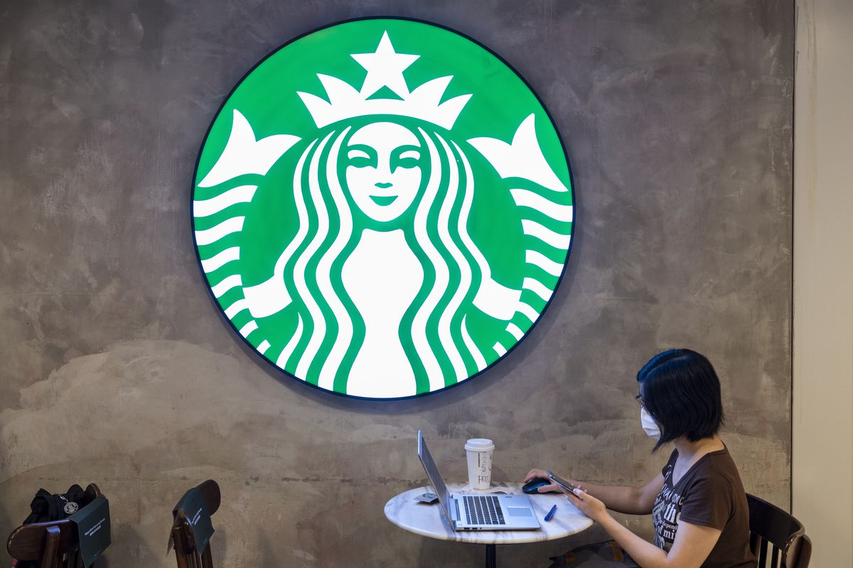 A masked woman with short dark hair sits at a marble cafe table, working on her laptop under an illuminated Starbucks logo.