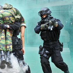 South Korean police SWAT team members run through smoke during an anti-terrorism exercise at Samsung Electronic's building in Seoul on Tuesday. In a rare conciliatory gesture after months of bitter hostility, North Korea said Monday it would restart family reunions and a stalled tourism program for South Koreans.