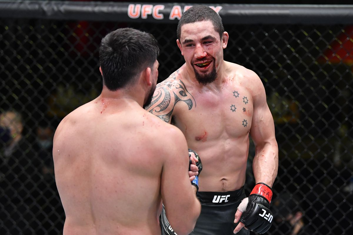 Robert Whittaker smiles at Kevlin Gastelum in the cage at UFC on ESPN 22.