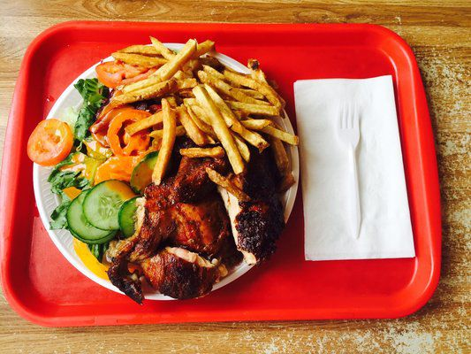 Roasted chicken with French fries and salad on a tray.