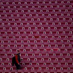 A photographer walks through empty stands before the game between the Utah Utes and the USC Trojans at Rice-Eccles Stadium in Salt Lake City on Saturday, Nov. 21, 2020.