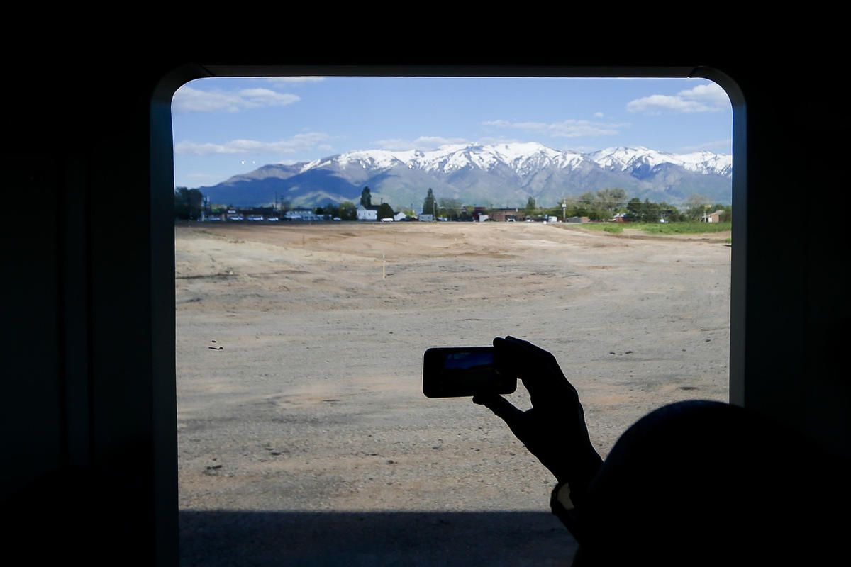 FILE - UTA Board of Trustees member Charles Henderson takes a photo of a site being developed outside the Clearfield Frontrunner Station on Wednesday, May 10, 2017.