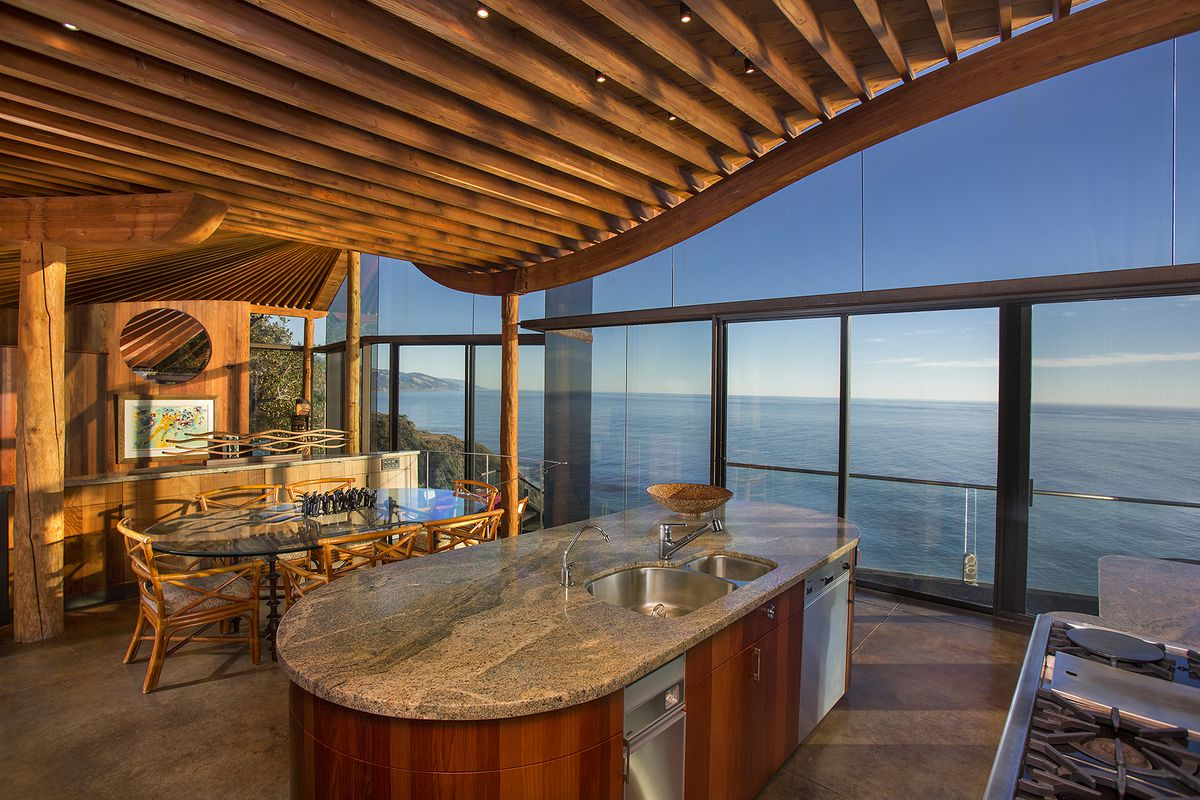 An interior of an oceanfront home with a curving slated roof, a kitchen island, and glass windows facing the ocean.