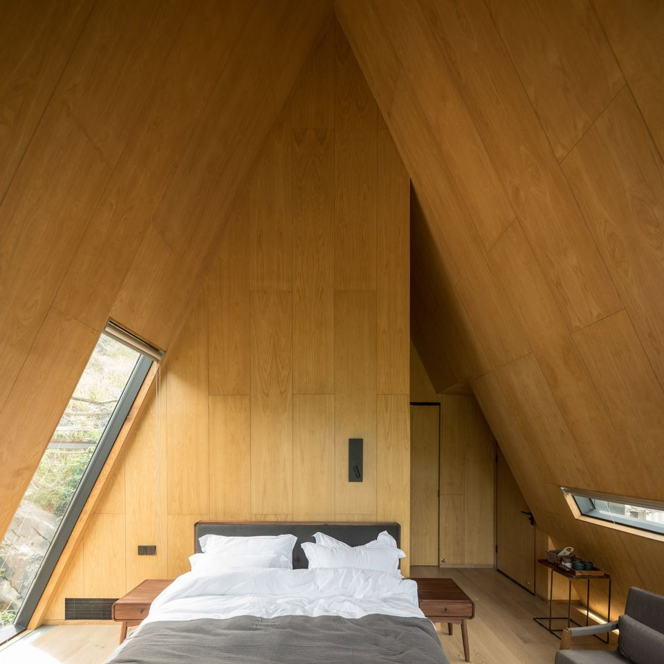 A bedroom that has wooden walls and a bed with white and grey bed linens. The ceiling and walls are sloped.