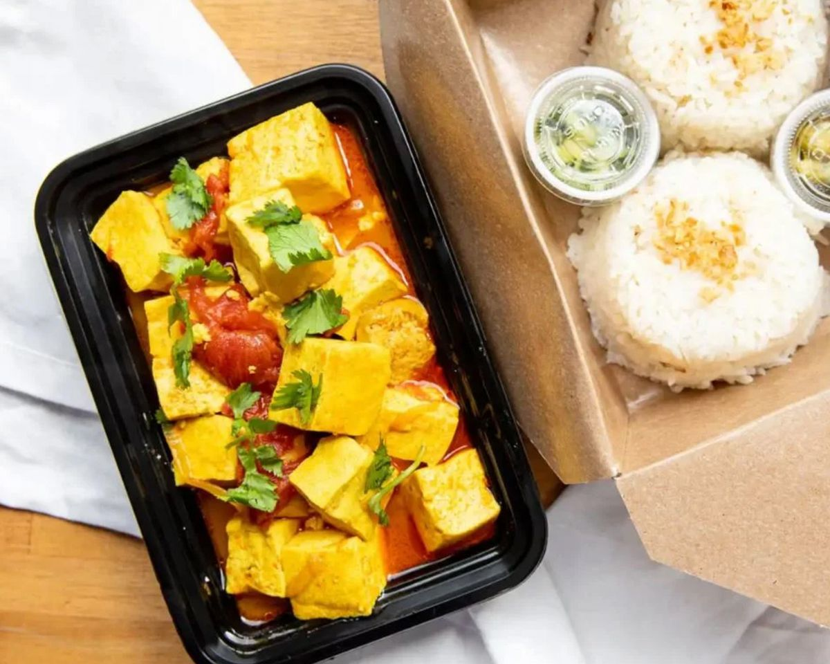 A picture of tofu curry and coconut rice in takeout containers from Top Burmese