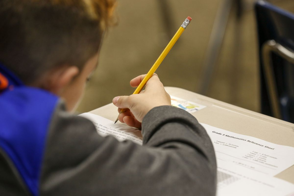 A student takes a test at their desk, writing with a number two pencil.