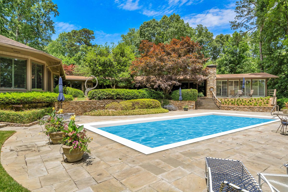 A backyard pool with a stone patio and a large midcentury beige house around it.