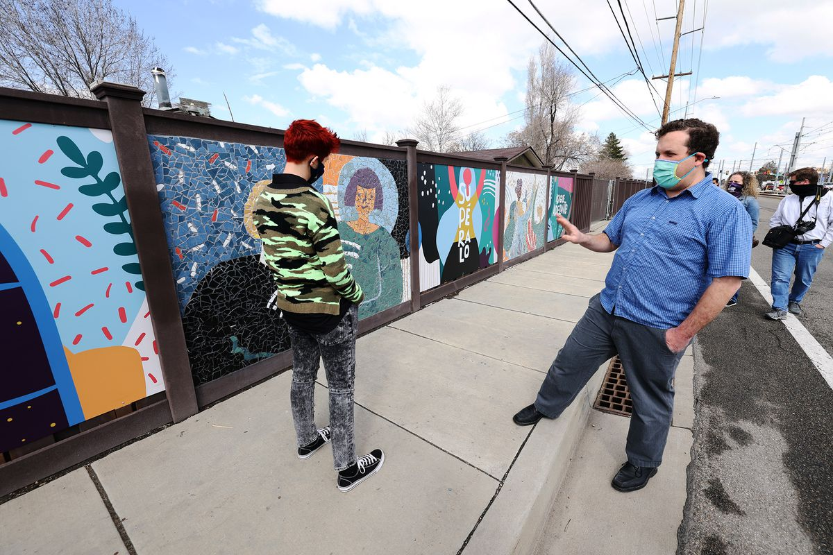 Project assistant Mati Simonds, left, and artist Roger Whiting, of Community Arts of Utah, stand near their mosaic mural on 2700 West between 3500 South and 3100 South in West Valley City on Tuesday, March 16, 2021.Earlier, Gov. Spencer Cox and West Valley Mayor Ron Bigalow held a bilingual press event at West Valley City Hall to unveil the mural, dedicated to those who have taken their own lives, and a media campaign to raise awareness of mental health and suicide prevention resources available to Utah's Latino community.