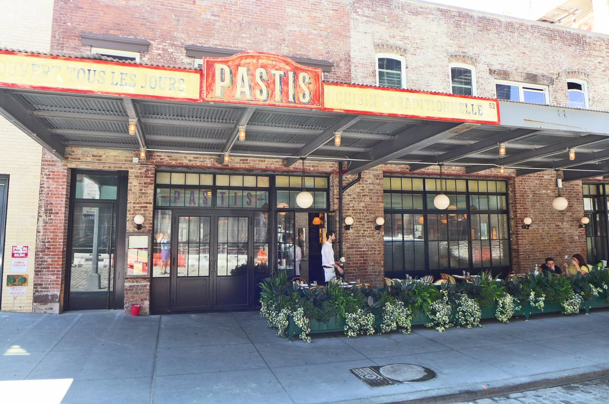 A restaurant exterior in Manhattan's Meat Packing District that looks like an old loading dock, with outdoor seating mainly empty in the foreground...