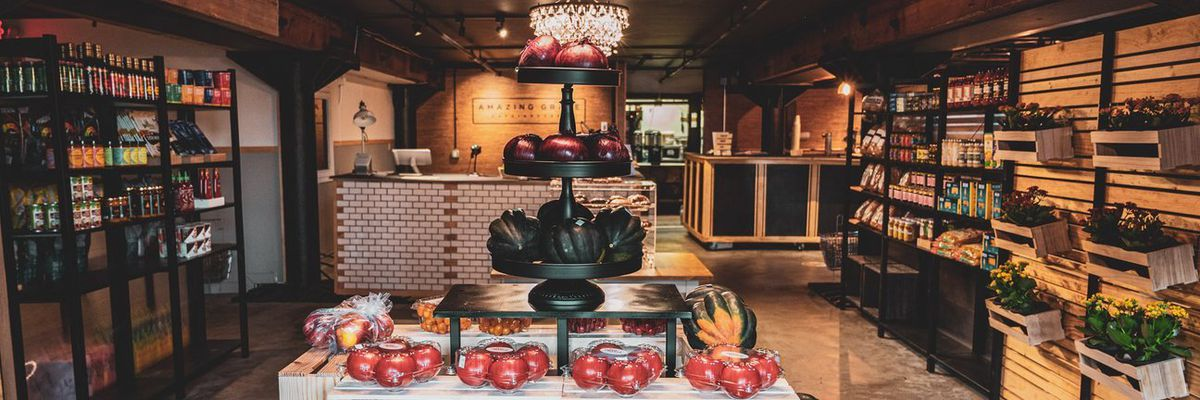 A pretty market with black shelves lined with goods. At the center of the room is a table with a tiered container showing off squash, red onions, and tomatoes. A glass ball adorned chandelier hangs over it. The room is tidy and inviting.