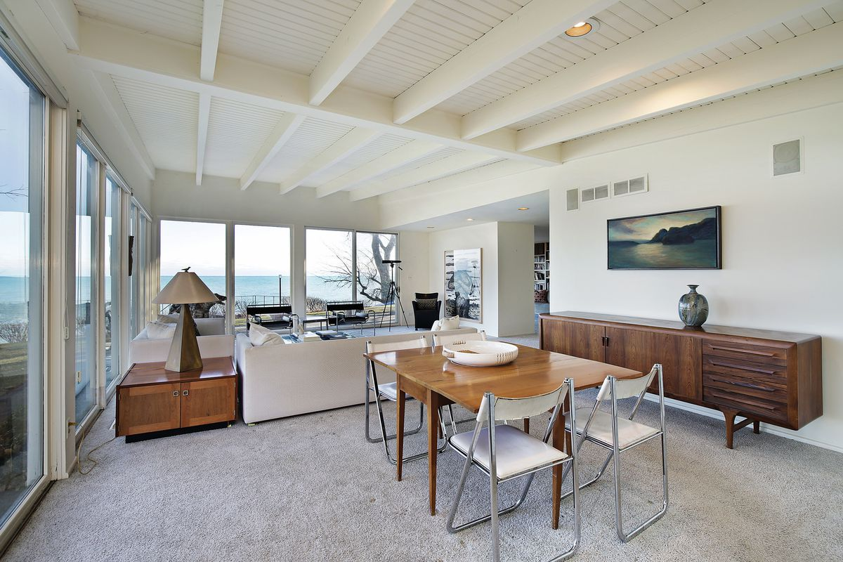 A wooden dining table stands on gray carpet in a midcentury living room with white wood beam ceilings above.