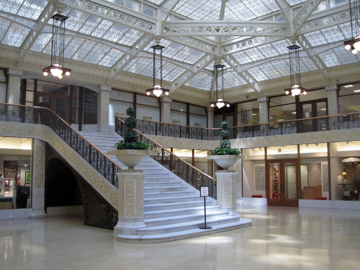 The Rookery by Frank Lloyd Wright. This is the interior of The Rookery. There is a large white staircase, multiple geometric light fixtures, and a glass ceiling with ornamentation.
