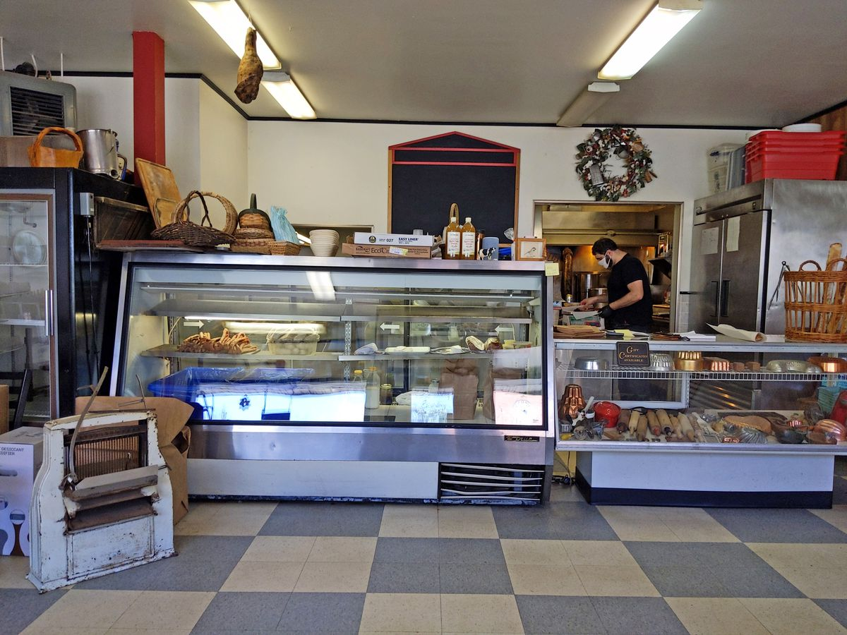 An old fashioned store with a glass case and man in black standing behind the counter not facing the camera.