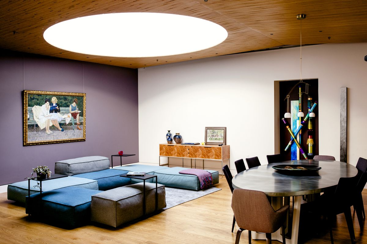 A living area with multiple colorful couches, a wooden table, chairs, and a large work of art on the wall. One of the walls is purple and the ceiling is wooden with a large circular white light.