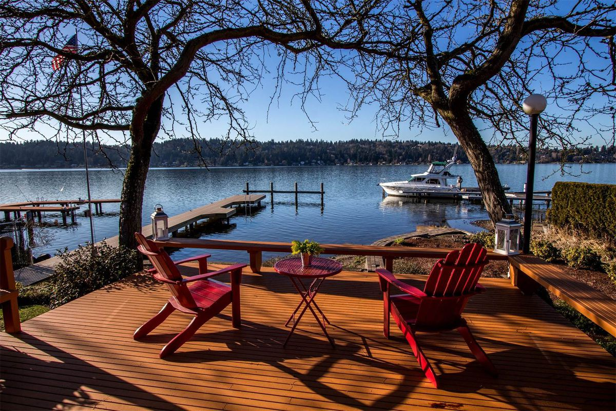 Two deck chairs and a table on a large patio overlooking Lake Washington