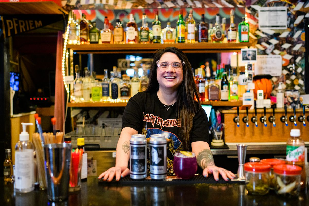 A woman with brown hair and glasses smiles from behind a bar