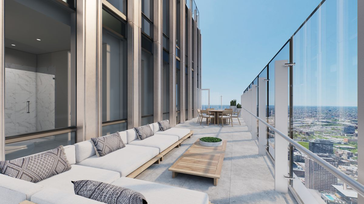 An outdoor terrace stretching along the side of a building. It has glass windbreaks and multiple seating areas.