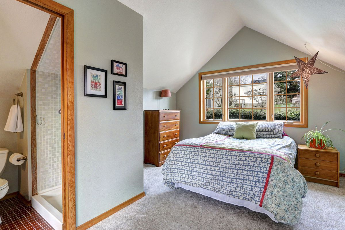 An upstairs bedroom with a window, a small bathroom, and vaulted ceilings