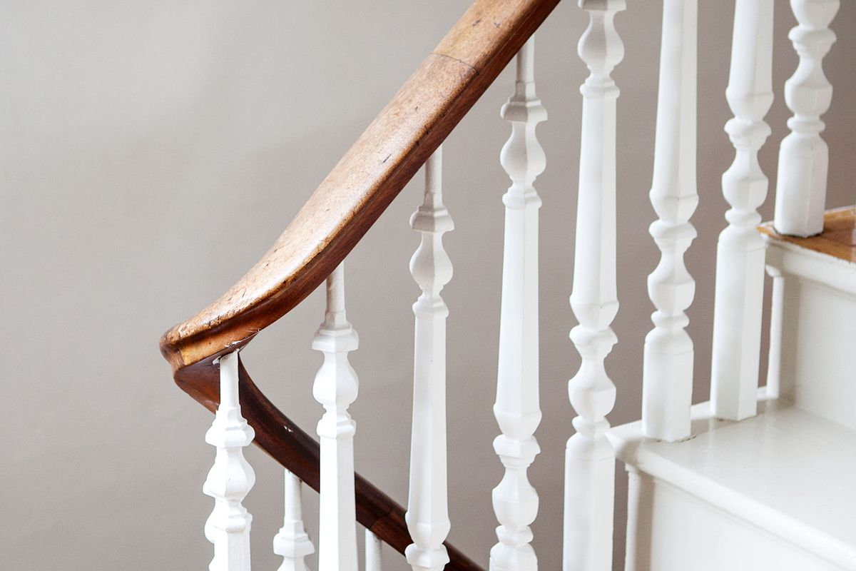 A tight shot of a wooden staircase, white and dark wood.