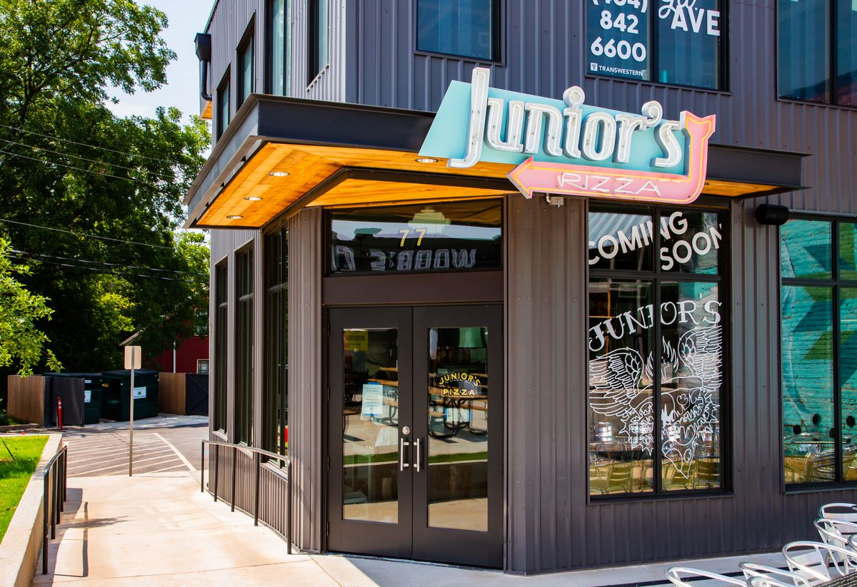 The outside entrance to Junior's Pizza with its neon sign