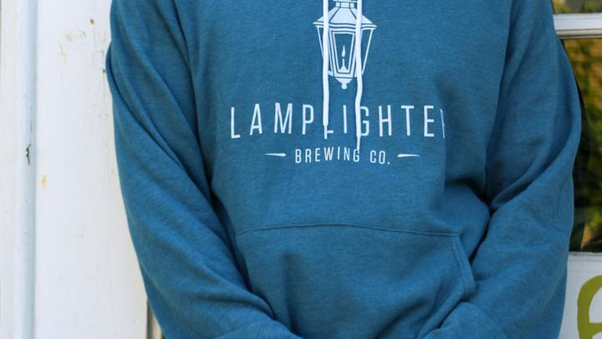 Light blue, almost turquoise, standard hoodie with kangaroo pocket and white strings. It features a white logo for Lamplighter Brewing Co., including old-fashioned street lamp imagery.