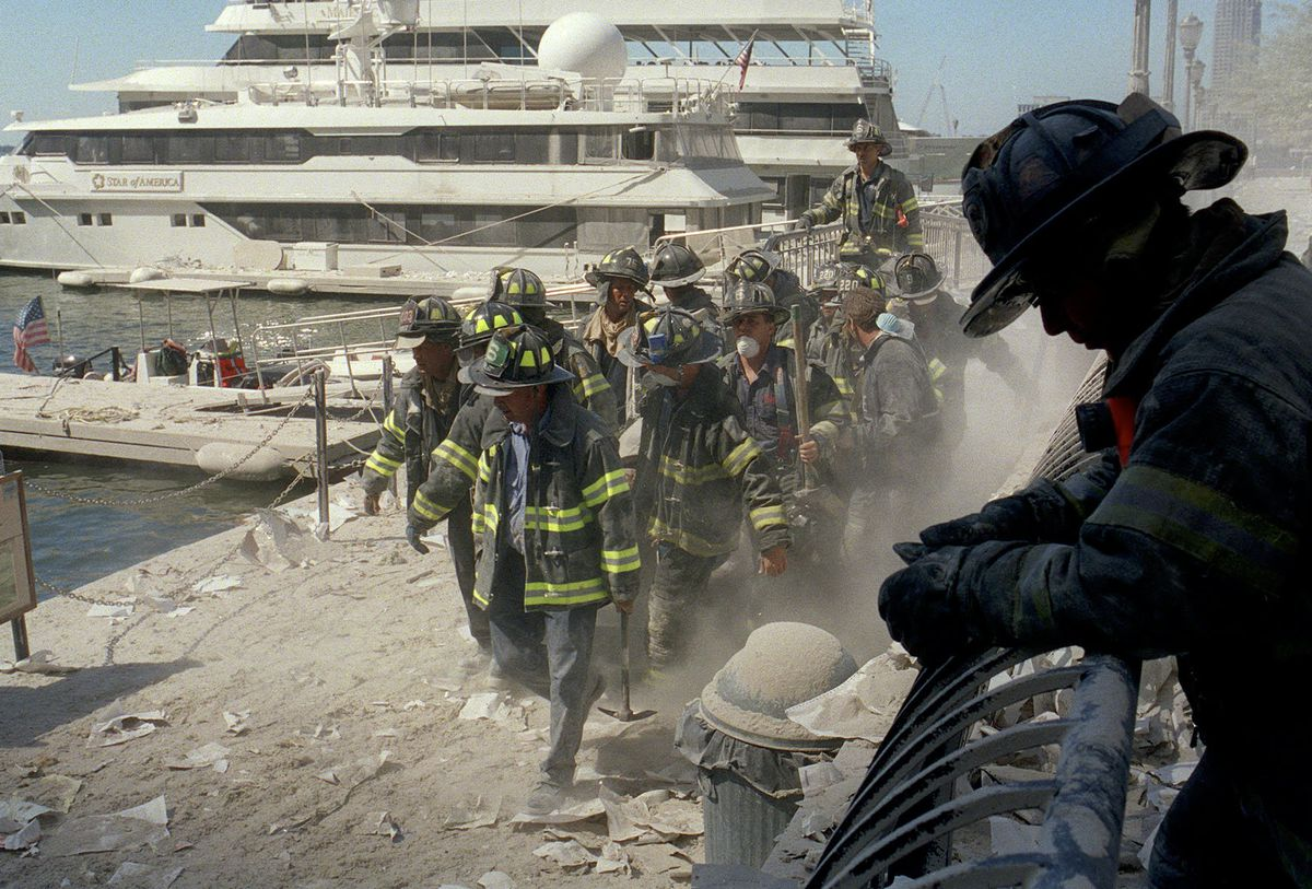 """New York City firefighters carrying an injured colleague to a boat on Sept. 11, 2001. """"Epicenters"""" includes a segment on maritime evacuations that fateful day."""