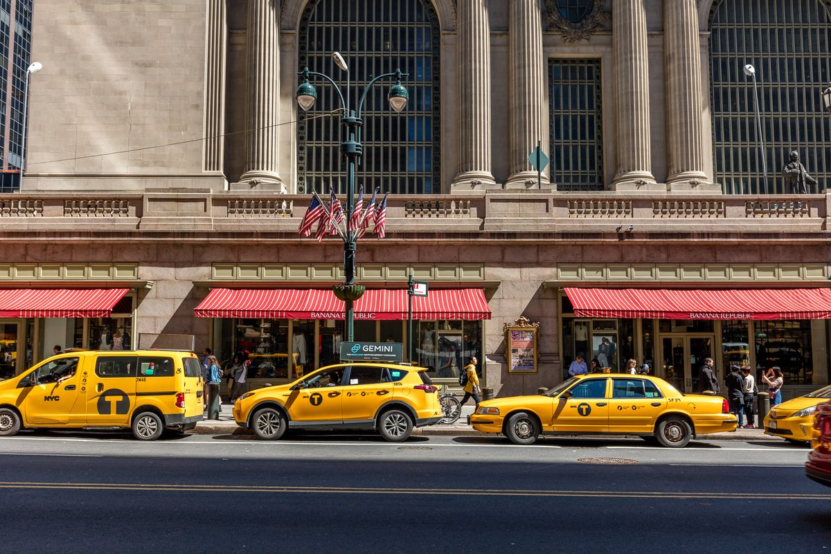 Three yellow taxi cabs lined up outside of Grand Central Terminal in Manhattan.
