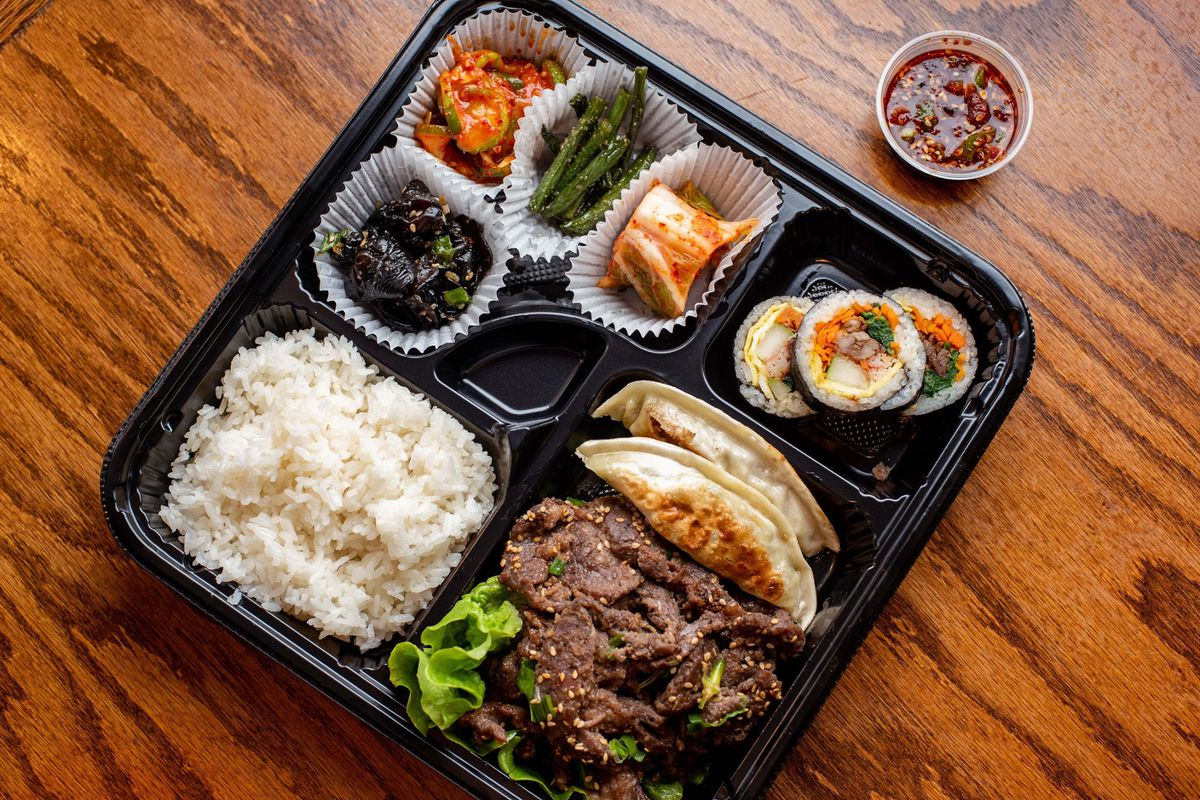 A black partitioned takeout container with white rice and beef bulgogi as main entrees alongside dumpling and banchan from Woo Nam Jeong Stone Bowl House in Doraville