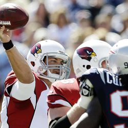 Arizona Cardinals quarterback Kevin Kolb, left, passes over New England Patriots linebacker Jermaine Cunningham (96) in the first quarter of an NFL football game, Sunday, Sept. 16, 2012, in Foxborough, Mass.