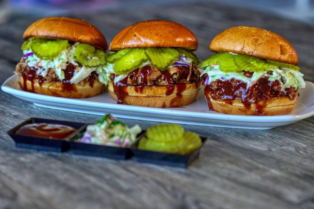 Three barbecue sandwiches on a white plate