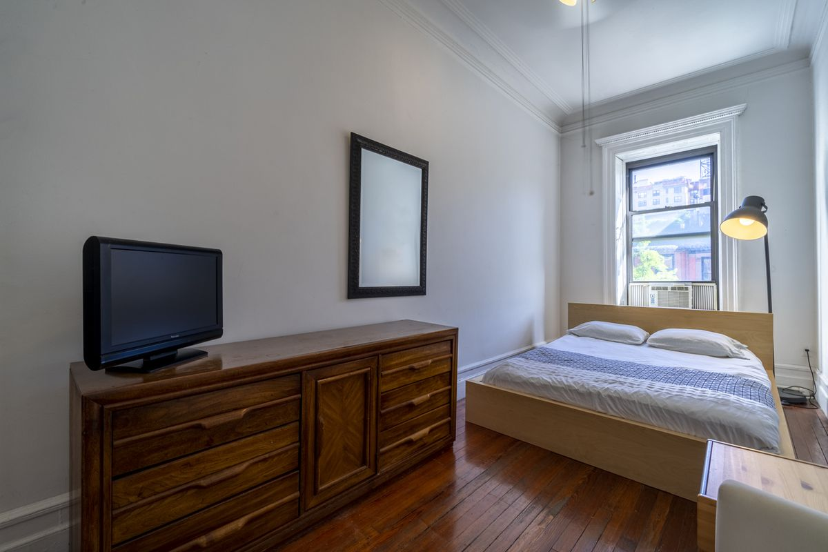 A bedroom with a medium-sized bed, a window with a small A/C unit, wooden cabinets, and hardwood floors.